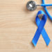 Blue ribbon and stethoscope on wooden background. Cancer awareness concept