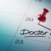 Concept image of a Calendar with a red push pin. Closeup shot of a thumbtack attached. The words Doctor written on a white notebook to remind you an important appointment.