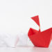 Leadership concept. red paper ship lead among white. One leader ship leads other ships.