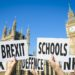 Hands holding signs protesting modern British social issues like Brexit, tax, education, defense, and health in front of the Houses of Parliament at Westminster Palace in London, United Kingdom