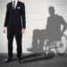 Businessman Standing Against White Brick Wall With Shadow Of A Disable Man Sitting On Wheelchair