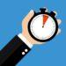 Hand mit Stoppuhr zeigt 5 Sekunden 5 Minuten oder 1 Stunde - Flat Design