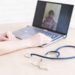 gp hosts an online appointment with an elderly quarantined patient at home. Female doctor at the desk talking to an elderly woman on a web camera and gives treatment recommendations.