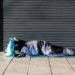 Sunderland / Great Britain - February 19, 2019: Homeless person asleep in a sleeping bag on a pavement sidewalk in front of a metal shutter.  Face not visable.