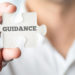 Close up Businessman Hand Holding Puzzle Piece with Conceptual Guidance Text In Front of the Camera.