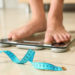 Tape in front of woman standing on floor scales indoors. Overweight problem